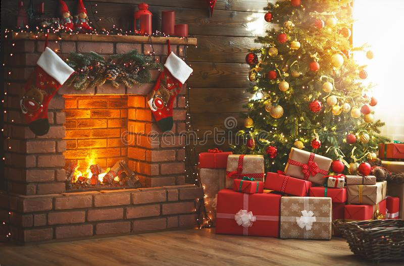 内部圣诞节 不可思议的发光的树,壁炉,礼物 免版税库存图片