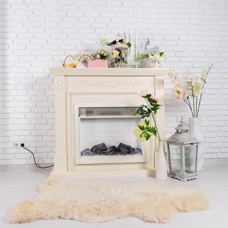 内部在有壁炉,花和软的一个轻的客厅 库存照片