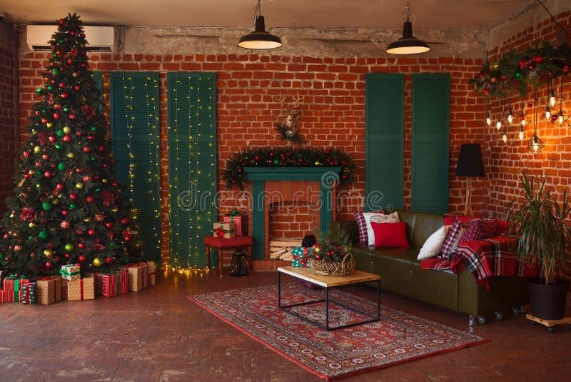 内部居住的现代空间 创造性的圣诞树、当代壁炉和大橄榄色的沙发在顶楼内部 免版税库存照片
