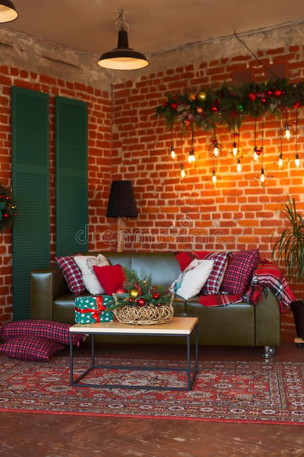 内部居住的现代空间 创造性的圣诞树、当代壁炉和大橄榄色的沙发在顶楼内部 免版税库存图片