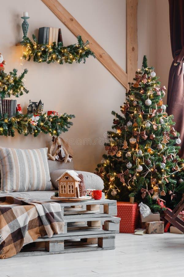 内部现代家庭客厅的镇静图象装饰了圣诞树和礼物,沙发,用毯子盖的桌 库存图片