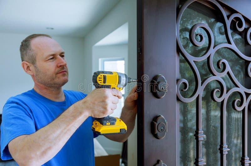 内部的设施与一把锁的在使用一把钻子螺丝刀的门叶子,举行的拧紧 免版税库存照片