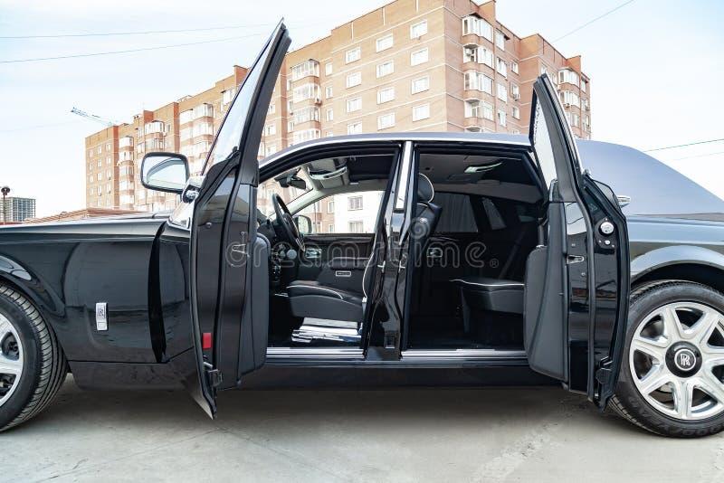 内部看法新一辆非常昂贵的汽车,有开门的一辆长的黑大型高级轿车,仪表板,方向盘,在停车处 免版税库存图片