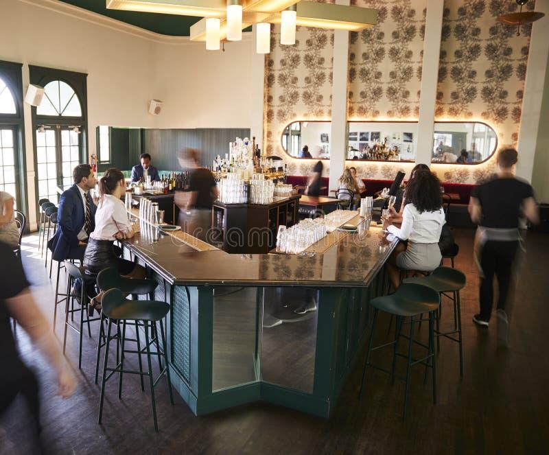 内部繁忙的鸡尾酒吧在有职员服务的顾客的餐馆 免版税库存照片