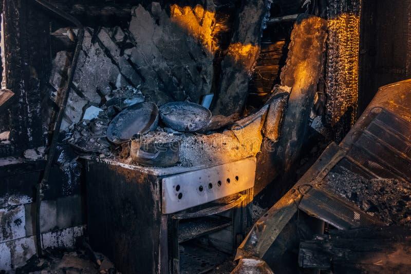 内部被烧的房子 被烧的火炉厨房、在黑煤灰的遗骸和家具 免版税库存照片