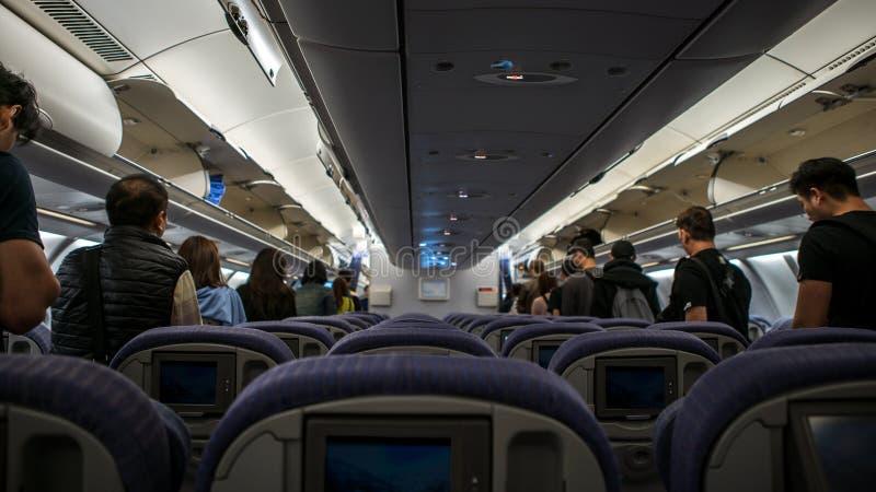内部飞机,走道的乘客走下飞机 免版税图库摄影