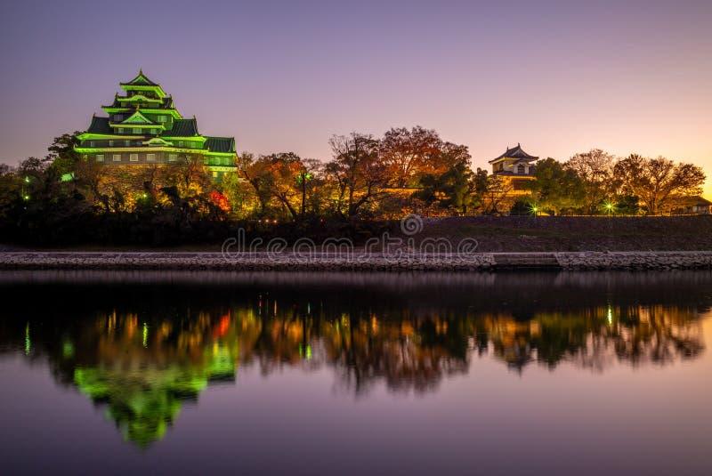 冈山城夜视图由河朝日的在日本 免版税库存照片