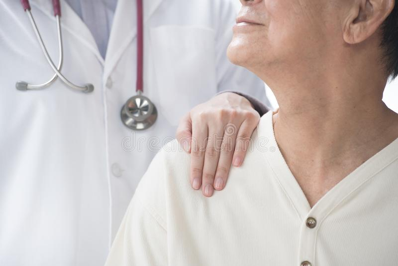 再保证资深患者和把手放的医生在patient's肩膀上 免版税图库摄影