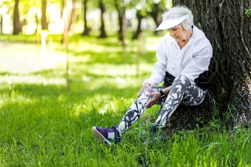 再创在训练以后的严肃的老妇人在绿色森林里 库存图片