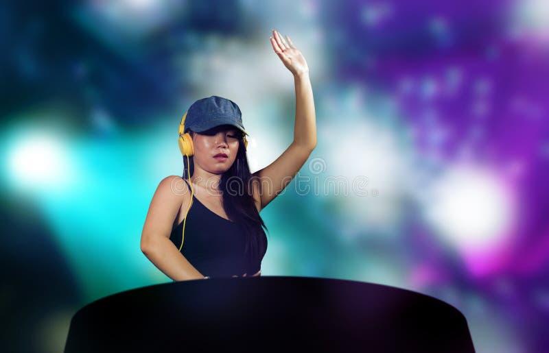 再混合使用节目播音员齿轮和耳机的年轻可爱和愉快的亚裔中国人DJ妇女在夜总会有光背景 免版税库存图片
