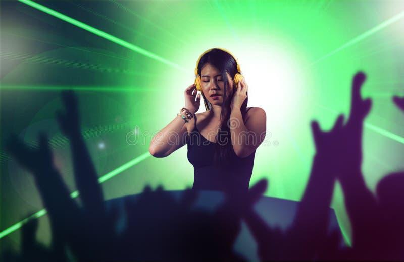 再混合使用节目播音员齿轮和耳机的年轻可爱和愉快的亚裔韩国DJ妇女在夜总会有光背景 库存图片