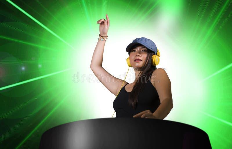 再混合使用节目播音员齿轮和耳机的年轻可爱和愉快的亚裔韩国DJ妇女在夜总会有光背景 图库摄影