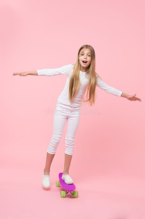 再生她的能量溜冰板运动 执行在桃红色背景的可爱的小孩踩滑板的把戏 r 免版税库存照片