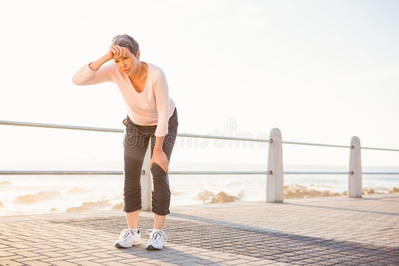 冒汗休息在散步的运动的妇女 库存图片