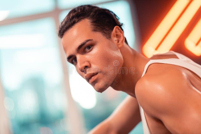 冒汗在他的面孔的严肃的帅哥 免版税库存图片