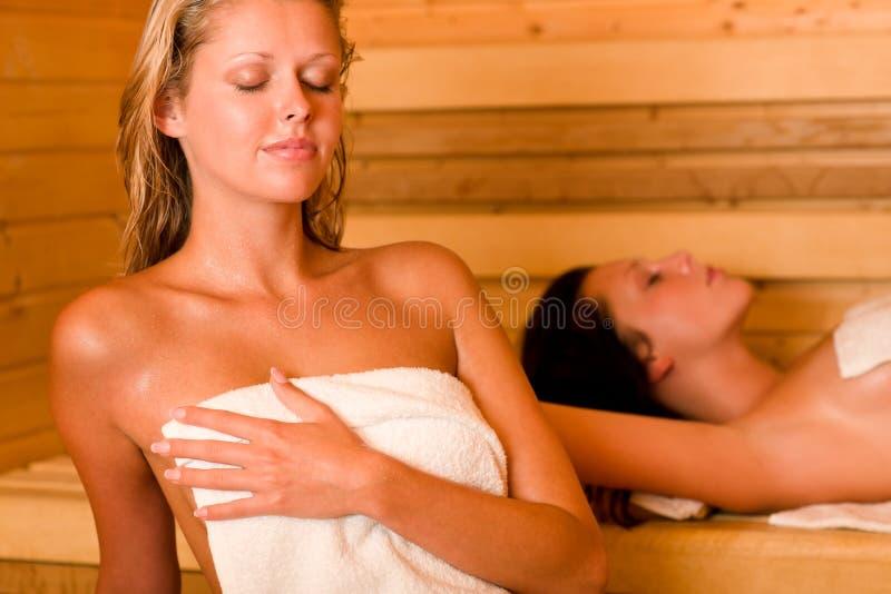 冒汗毛巾二妇女的报道的松弛蒸汽浴 库存照片