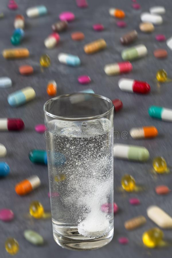 冒泡片剂在与泡影与多彩多姿的药片和胶囊的水中在灰色板岩背景 库存照片