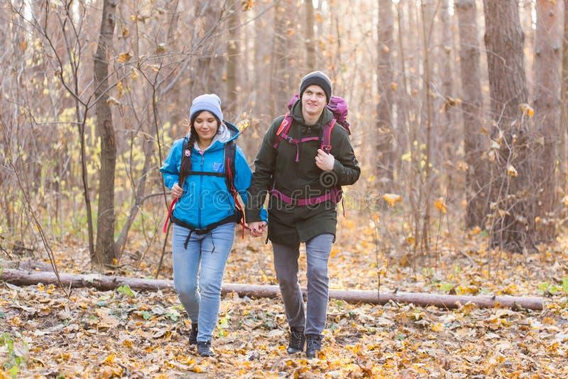 冒险、旅行、旅游业、远足和人概念-走与在自然的秋天的背包的微笑的夫妇 库存照片