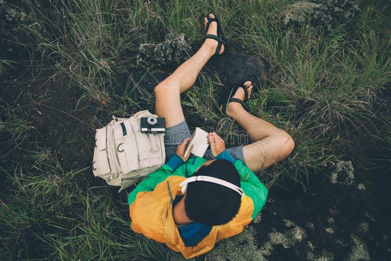 冒险坐与背包,照片照相机,听的音乐和写在笔记本,顶视图的人 库存照片