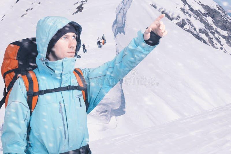 冒险的年轻人画象冬天山腰视图指出的 挡雪板走艰难为freeride 库存照片