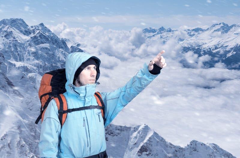 冒险的年轻人画象冬天山顶视图指出的 库存图片