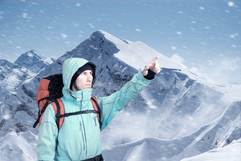 冒险的年轻人画象冬天山顶视图指出的 库存照片