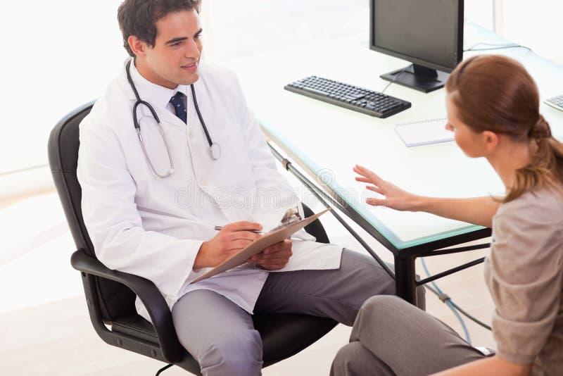 写下他的患者描述的症状的医生 免版税库存图片
