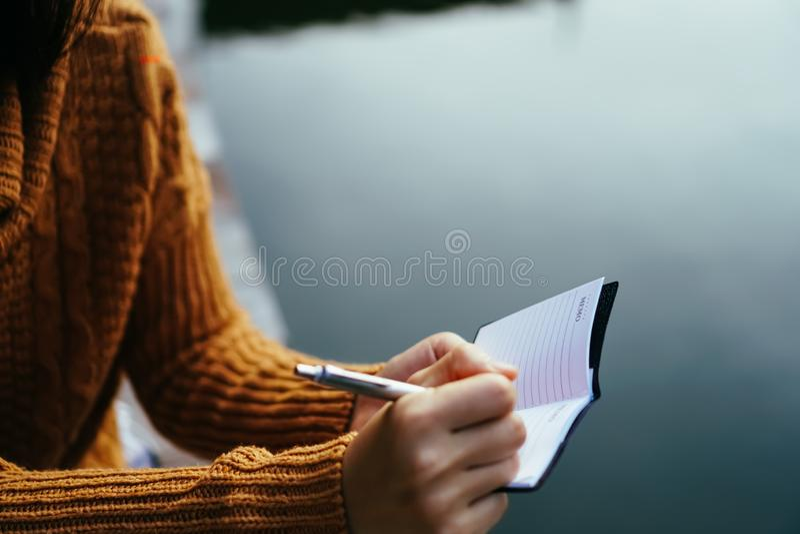 写下在小白色备忘录笔记本的妇女手 图库摄影
