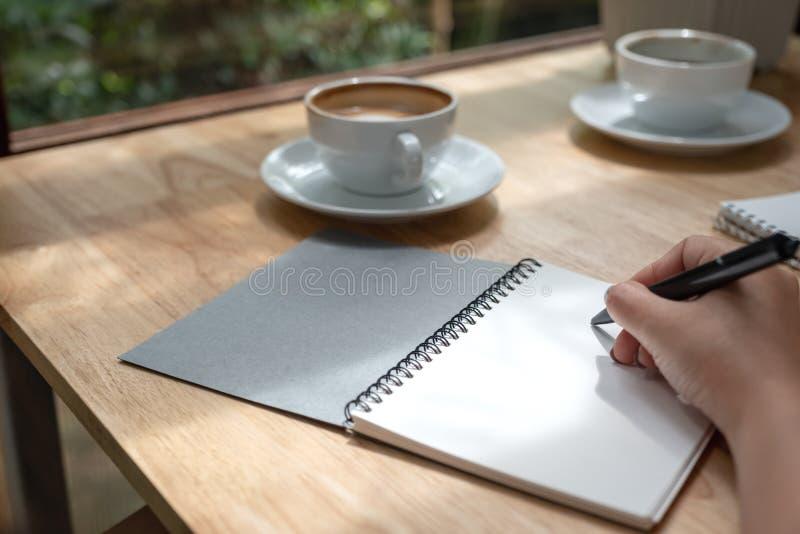 写下在有咖啡杯的一个白色空白的笔记本的手在木桌上 免版税库存图片