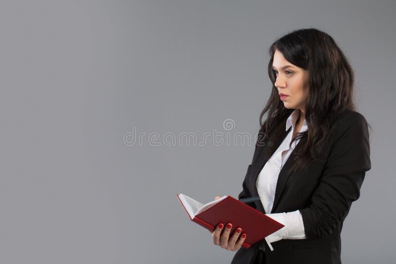 写下笔记的年轻女商人给笔记薄 相当在站立的剪贴板的周道的企业夫人文字  库存图片