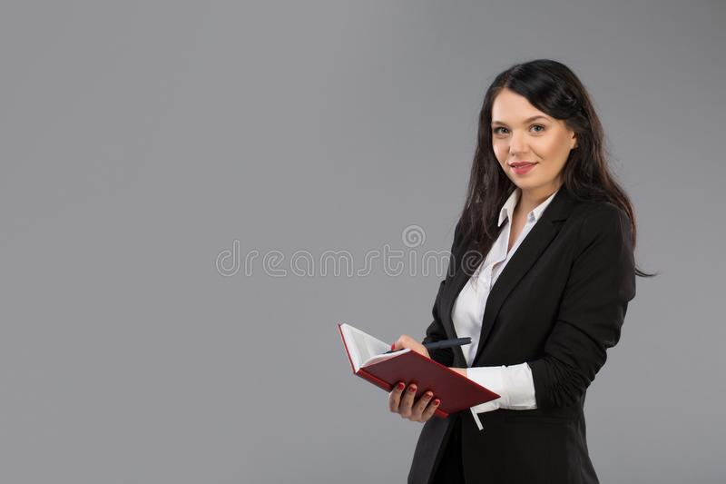 写下笔记的年轻女商人给笔记薄 相当在站立的剪贴板的周道的企业夫人文字  免版税库存照片