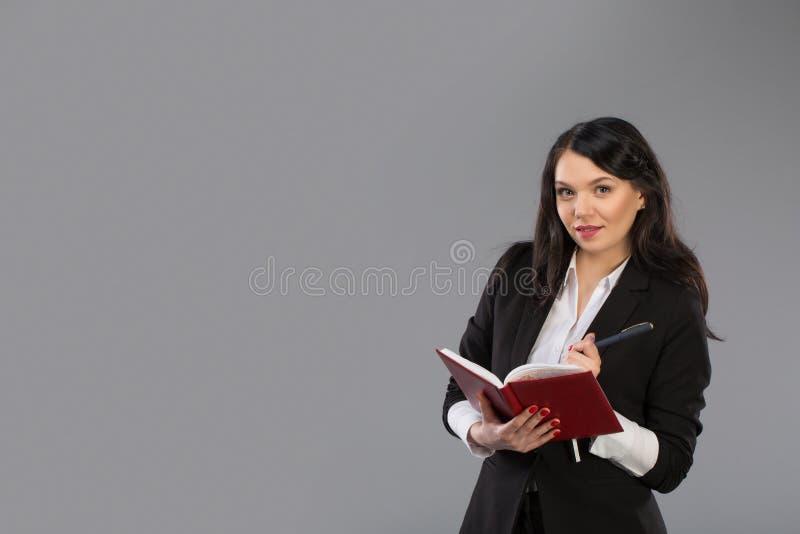 写下笔记的年轻女商人给笔记薄 相当在站立的剪贴板的周道的企业夫人文字  免版税图库摄影