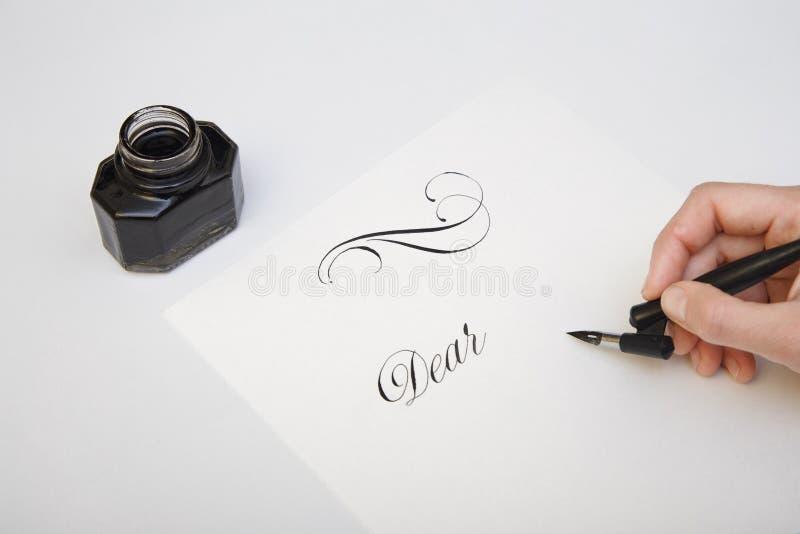 写与翎毛钢笔 写的过程溢出的墨水和钢笔概念图象 葡萄酒鸟嘴笔和墨水池 库存照片