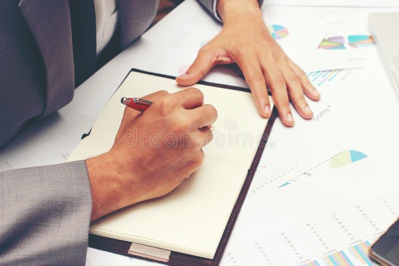 写业务报告的商人在有红色笔的空白的笔记本在书桌办公室 企业概念: 库存照片