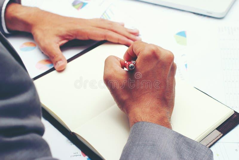 写业务报告的商人在有红色笔的空白的笔记本在书桌办公室 企业概念: 免版税库存照片