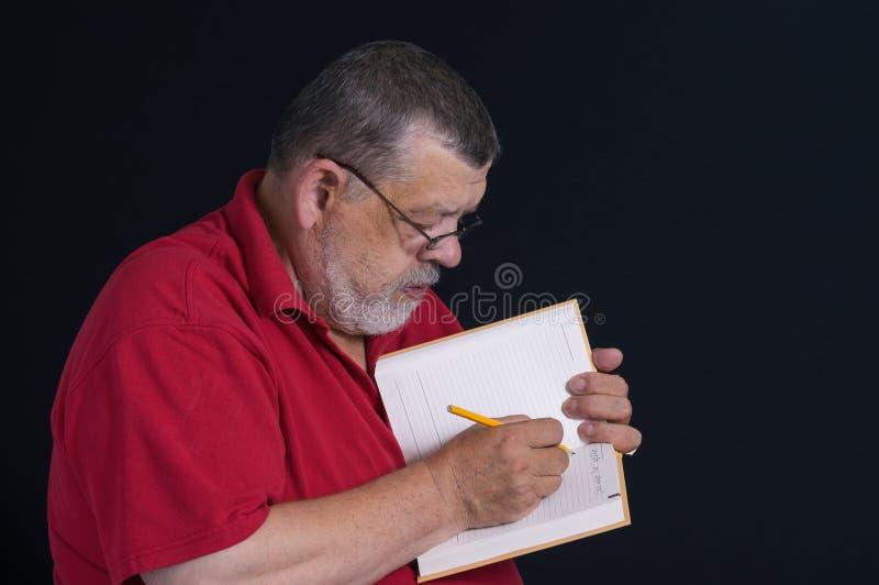 写信的一个有胡子的前辈的画象给他的儿子在笔记本 免版税图库摄影