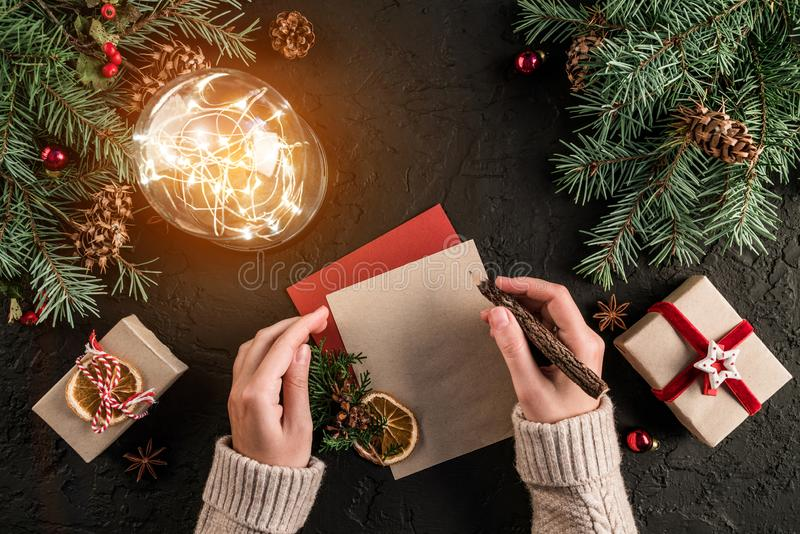 写信的女性手给圣诞老人在与圣诞礼物的黑暗的背景,发光的球,冷杉分支,黄麻丝球  免版税库存图片