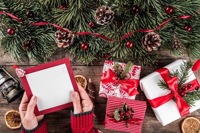 写信的女性手给圣诞老人在与圣诞礼物,冷杉分支,灯,杉木锥体的假日木背景 库存图片