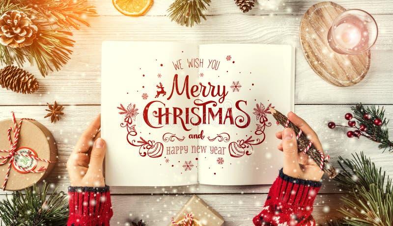 写信的女性手给圣诞老人 圣诞节与节日书籍,铅笔,杉木锥体,在白色背景的礼物的冷杉分支 免版税库存照片