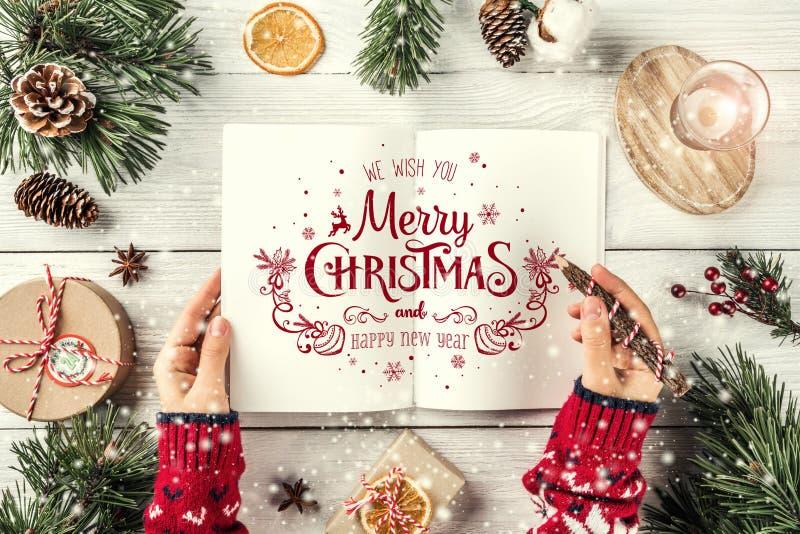 写信的女性手给圣诞老人 圣诞节与节日书籍,铅笔,杉木锥体,在白色背景的礼物的冷杉分支 免版税库存图片