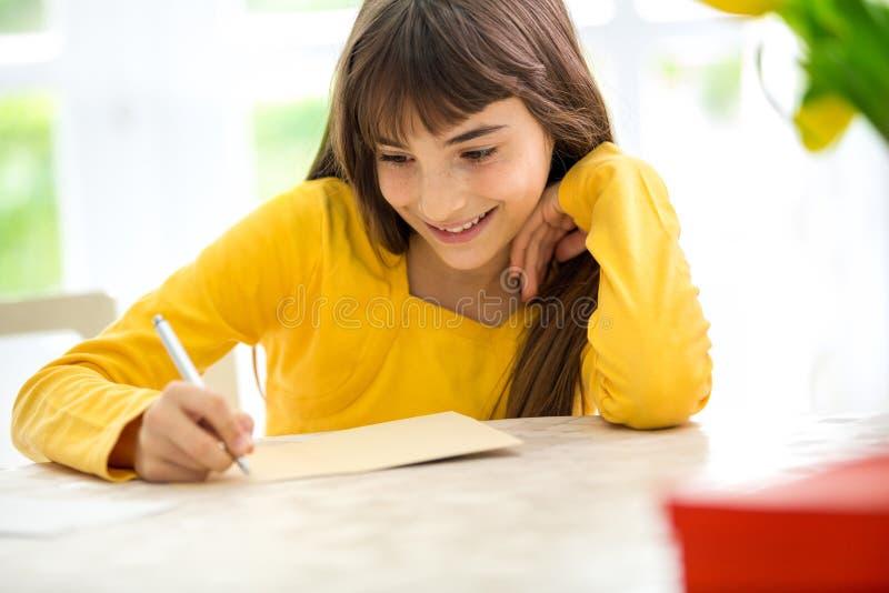 写信的逗人喜爱的女孩 图库摄影