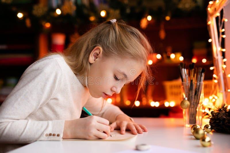 写信给圣诞老人项目或画某事的白肤金发的儿童女孩在与温暖的黄色bokeh的背景 圣诞节和 免版税图库摄影