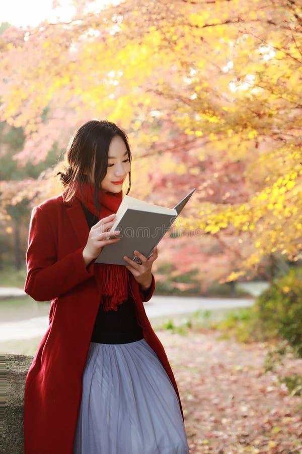 写入自然是我的爱好,美丽的女孩读了书坐石头在公园 免版税库存图片