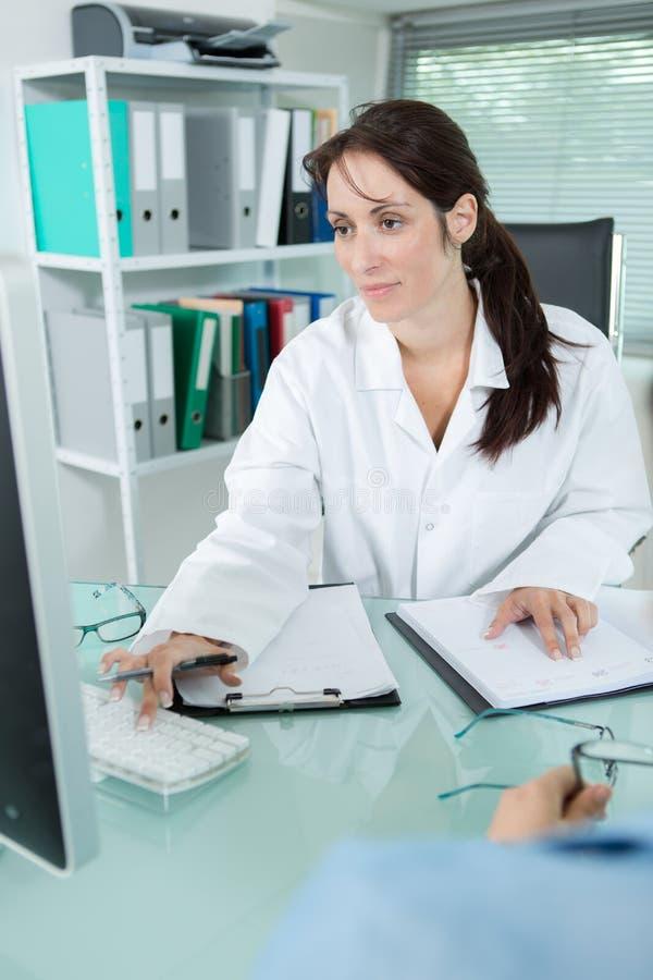 写医疗处方的女性医生坐在办公室 免版税库存图片