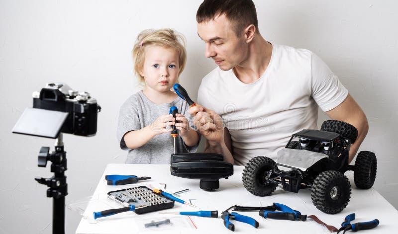 写博克的录影:在一个无线电操纵的汽车儿童车的修理期间,爸爸采取与一个小女儿的一次可笑的采访 免版税库存照片