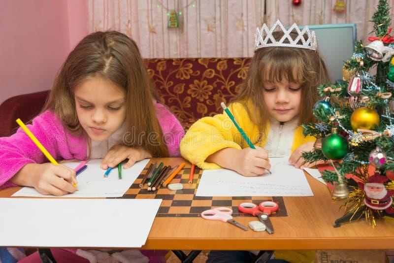 写圣诞节问候的两个女孩在家坐上写字在桌上 库存照片