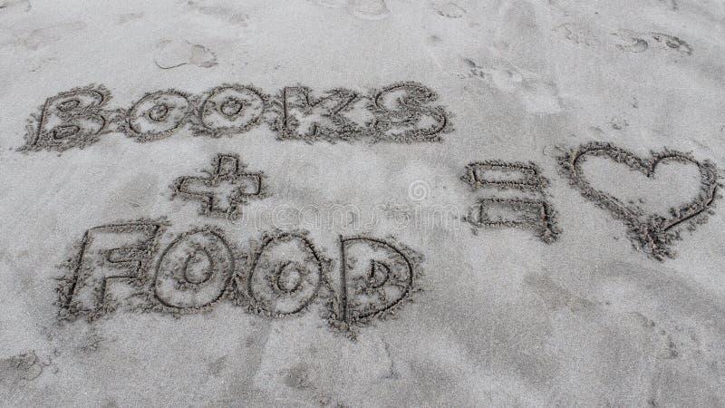 写在关于书和食物的沙子 免版税库存照片