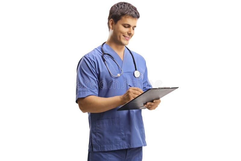 写在剪贴板的快乐的男性军医 免版税图库摄影