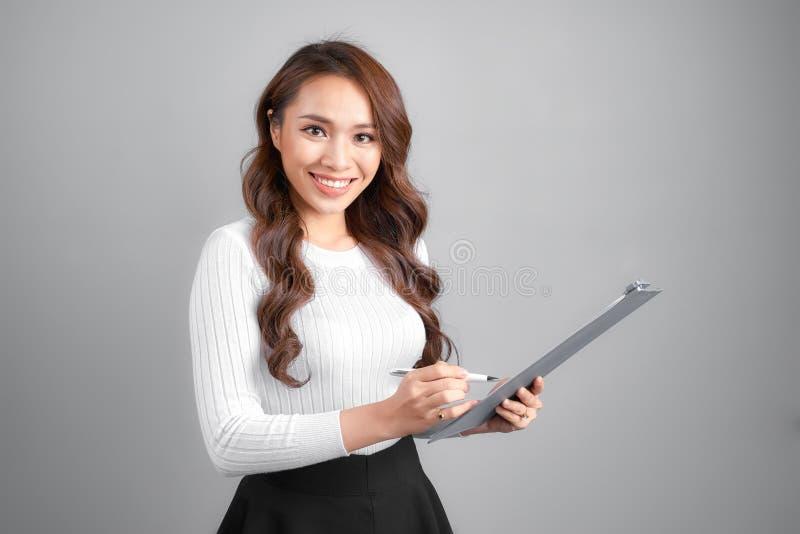 写在剪贴板的愉快的微笑的快乐的年轻女实业家,隔绝在白色背景 免版税库存图片