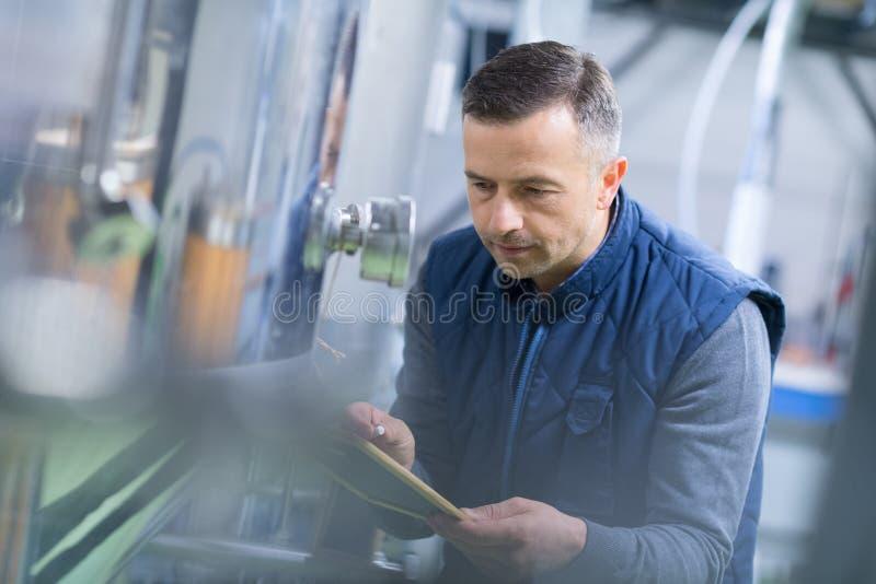 写在剪贴板的成熟男性审查员在工厂 免版税图库摄影
